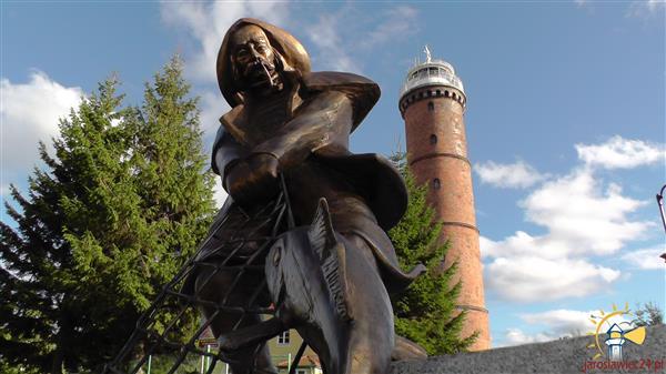 Posąg rybaka w centrum Jarosławca, w tle latarnia morska.